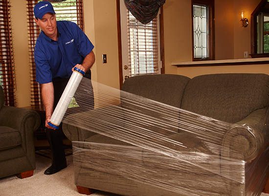 Man Shrink Wrapping Couch